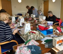 A medley of projects being worked at this table: Tracey`s Cushion, Glenis' Suffolk Puff Father Christmas and Lis` Table Centre